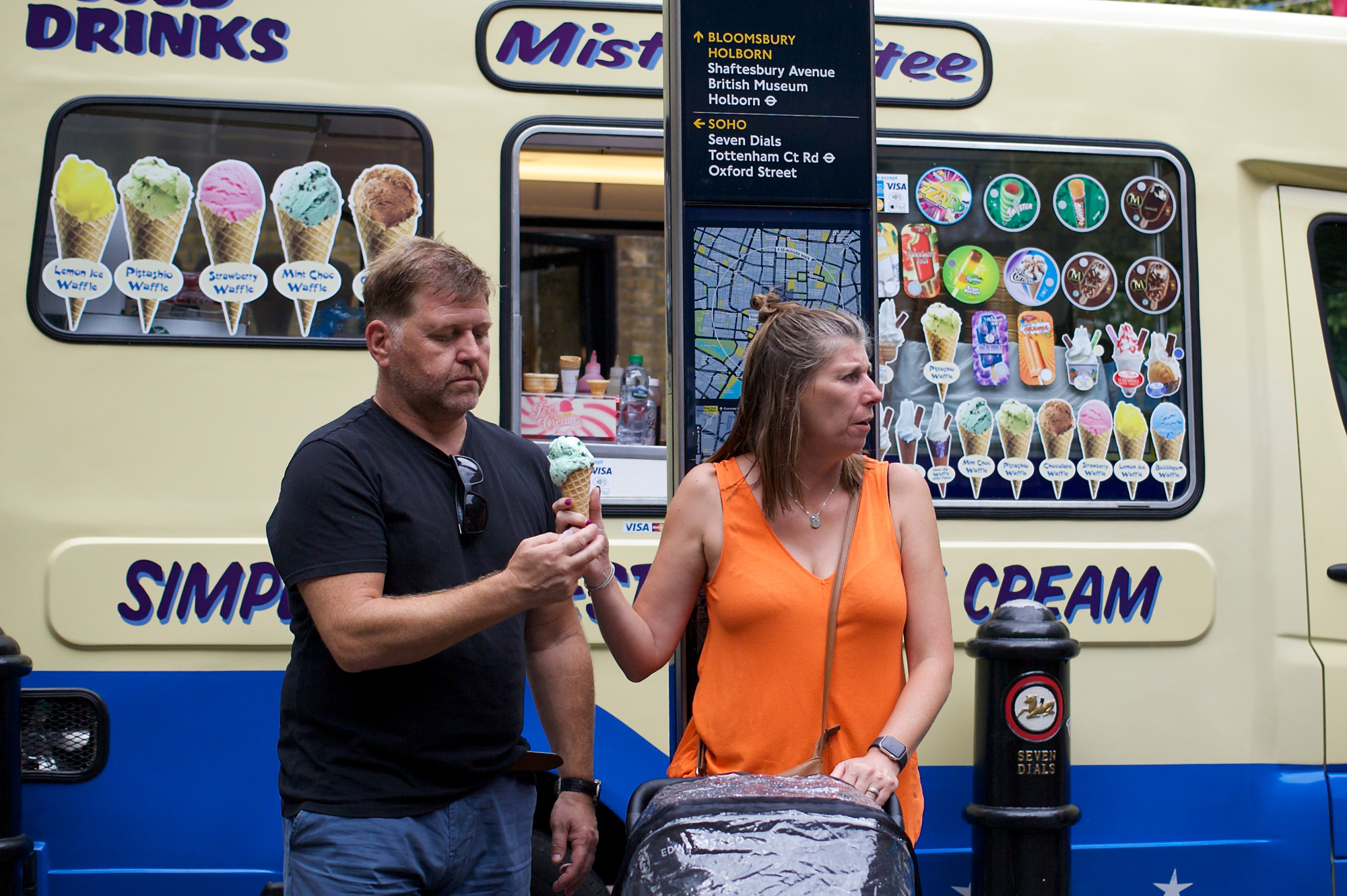 woman passes ice cream to man, looking away from him
